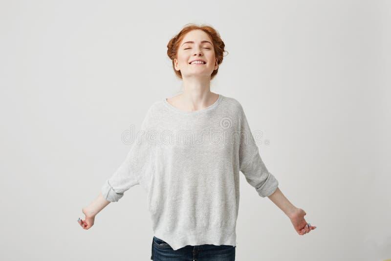 Ritratto di giovane ragazza felice della testarossa che sorride con gli occhi chiusi sopra fondo bianco immagine stock