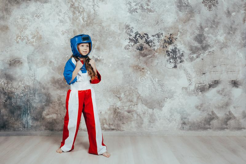 Ritratto di giovane ragazza femminile sorridente del taekwondo contro una parete di lerciume immagini stock libere da diritti