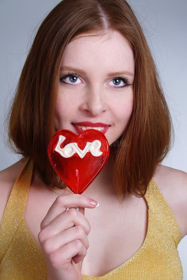 Ritratto di giovane ragazza graziosa che tiene un lollipop fotografia stock