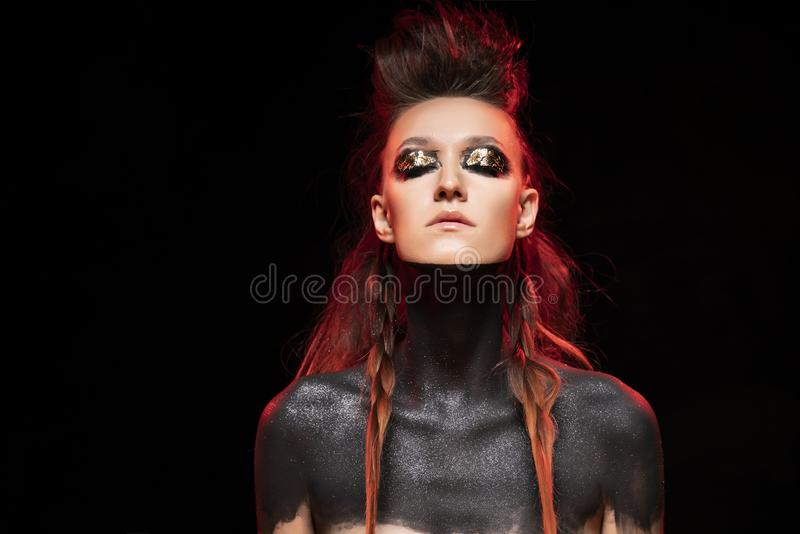 Ritratto di giovane ragazza selvaggia Le spalle ed il collo nudi sono coperti di pittura nera Trucco concettuale con la foglia di fotografia stock libera da diritti