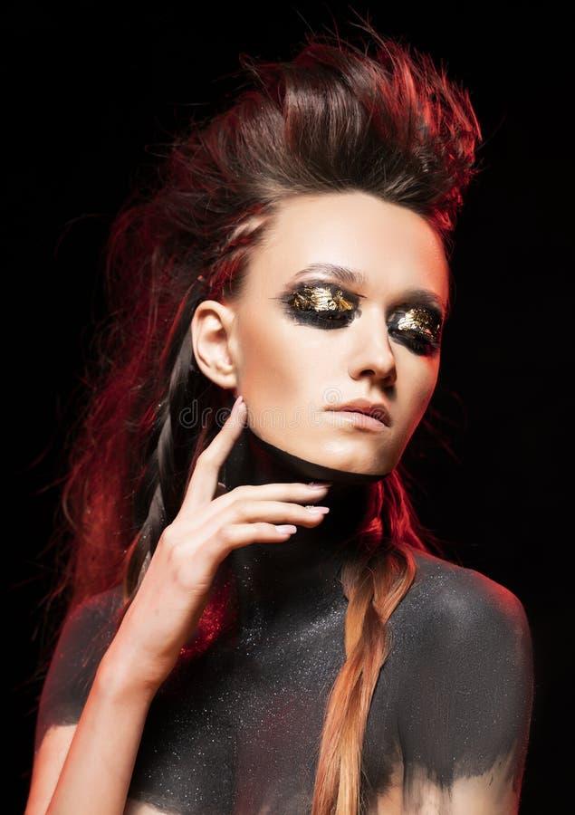 Ritratto di giovane ragazza selvaggia Le spalle ed il collo nudi sono coperti di pittura nera Trucco concettuale con la foglia di immagini stock libere da diritti