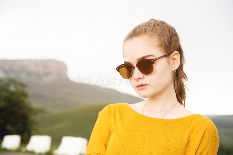 Ritratto di giovane ragazza seria attraente in occhiali da sole contro lo sfondo delle rocce e del cielo Serietà in fotografia stock