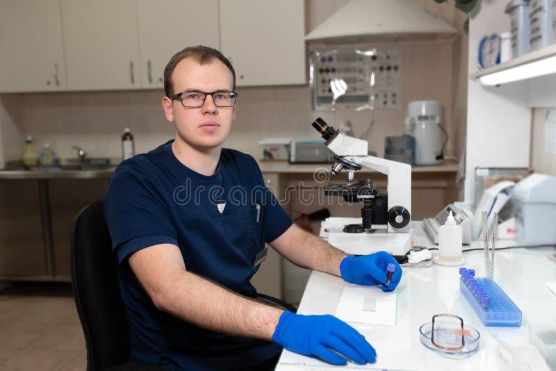 Ritratto di giovane scienziato maschio caucasico, del lavoratore medico, della tecnologia o degli impianti del dottorando in labo fotografia stock