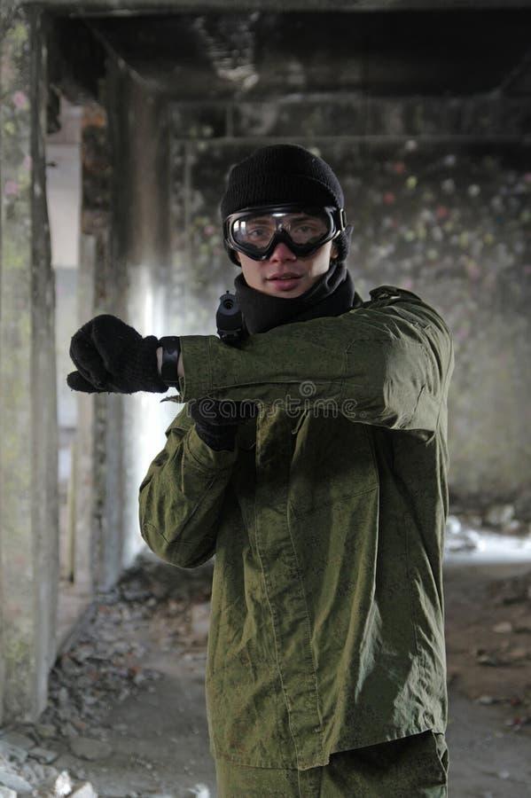 Ritratto di giovane soldato che indica con la pistola fotografia stock libera da diritti