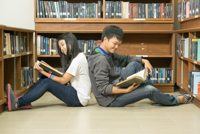 Ritratto di giovane studente serio che legge un libro in una biblioteca immagini stock
