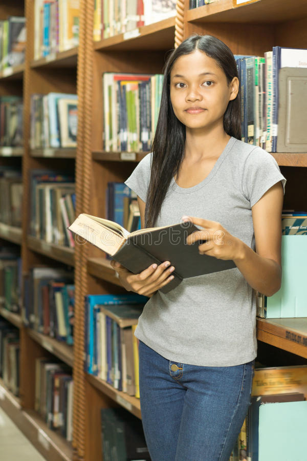 Ritratto di giovane studente serio che legge un libro in una biblioteca immagini stock libere da diritti