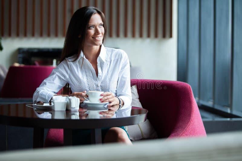 Ritratto di giovane tè bevente femminile splendido e di sguardo con il sorriso dalla finestra della caffetteria mentre godendola  immagini stock
