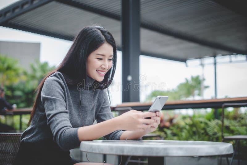 Ritratto di giovane telefono cellulare di uso della donna di affari mentre sedendosi i immagine stock