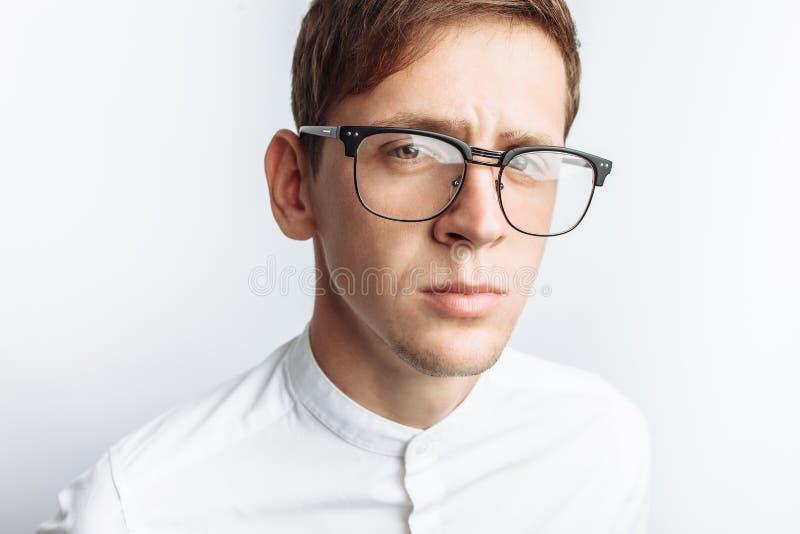 Ritratto di giovane tipo attraente in vetri, in camicia bianca, isolata su fondo bianco, per la pubblicità, inserzione del testo fotografia stock libera da diritti