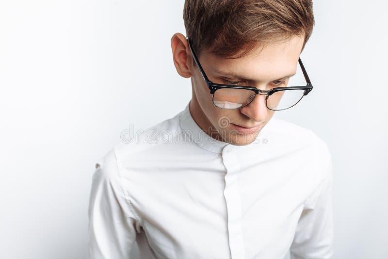 Ritratto di giovane tipo attraente in vetri, in camicia bianca, isolata su fondo bianco, per la pubblicità, inserzione del testo immagine stock libera da diritti