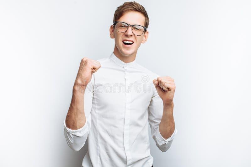 Ritratto di giovane tipo attraente in vetri che descrivono gioia, gesturing successo, in camicia bianca isolata su fondo bianco,  fotografia stock libera da diritti