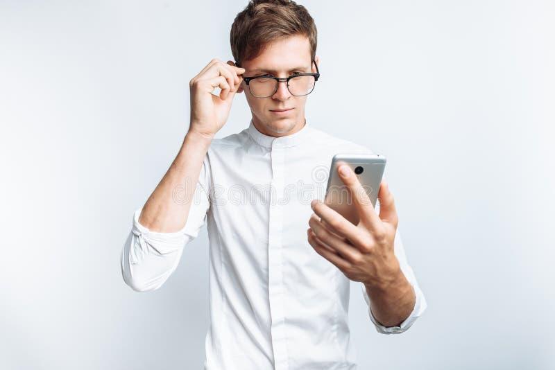 Ritratto di giovane tipo attraente in vetri che esaminano telefono, in camicia bianca isolata su fondo bianco, per la pubblicità, fotografia stock libera da diritti