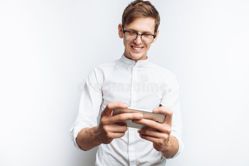 Ritratto di giovane tipo attraente in vetri che giocano sul telefono, in camicia bianca isolata su fondo bianco, per annunciare, immagine stock libera da diritti