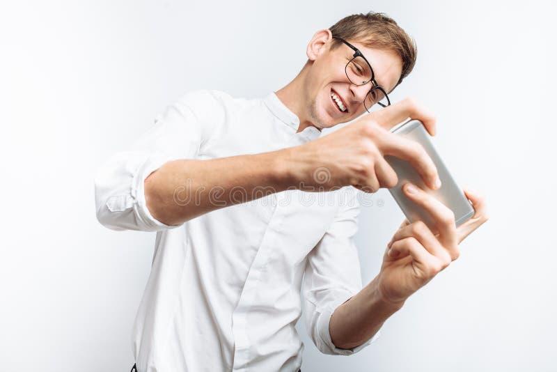 Ritratto di giovane tipo attraente in vetri che giocano sul telefono, in camicia bianca isolata su fondo bianco, per annunciare, immagini stock