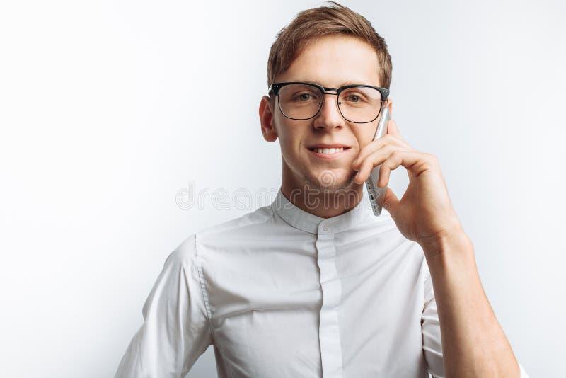 Ritratto di giovane tipo attraente in vetri che parla sul telefono e che descrive gioia, in camicia bianca isolata su fondo bianc fotografia stock