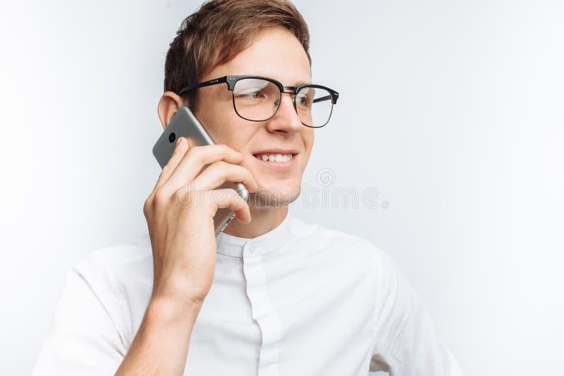 Ritratto di giovane tipo attraente in vetri che parla sul telefono e che descrive gioia, in camicia bianca isolata su fondo bianc fotografia stock libera da diritti