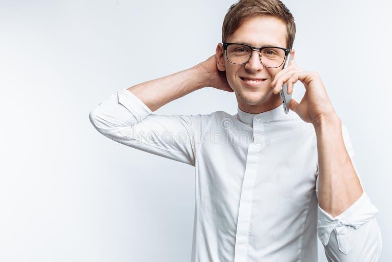 Ritratto di giovane tipo attraente in vetri che parla sul telefono e che descrive gioia, in camicia bianca isolata su fondo bianc immagini stock libere da diritti