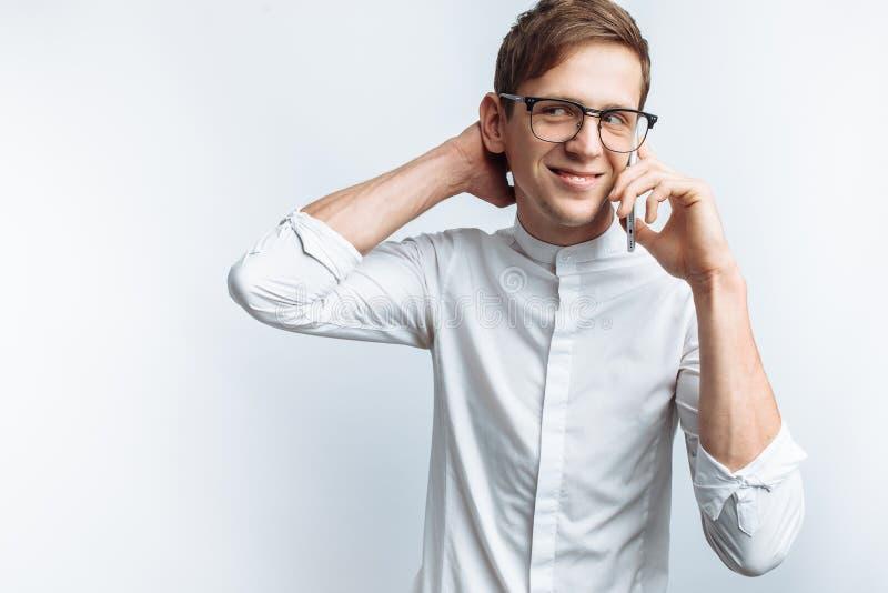 Ritratto di giovane tipo attraente in vetri che parla sul telefono e che descrive gioia, in camicia bianca isolata su fondo bianc immagine stock