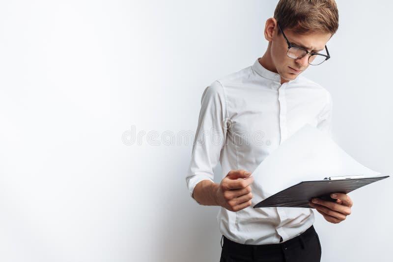 Ritratto di giovane tipo attraente in vetri, in una camicia bianca, con una cartella in sue mani e l'esame lei, isolato su un bri fotografia stock libera da diritti