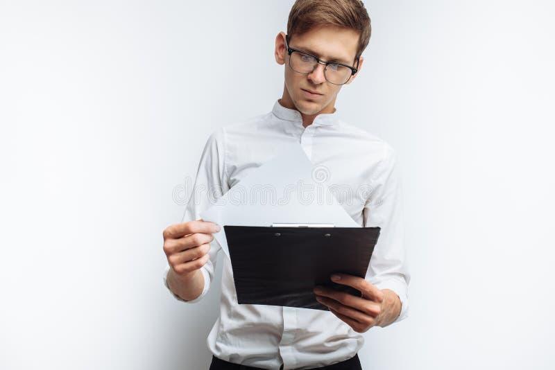 Ritratto di giovane tipo attraente in vetri, in una camicia bianca, con una cartella in sue mani e l'esame lei, isolato su un bri fotografia stock