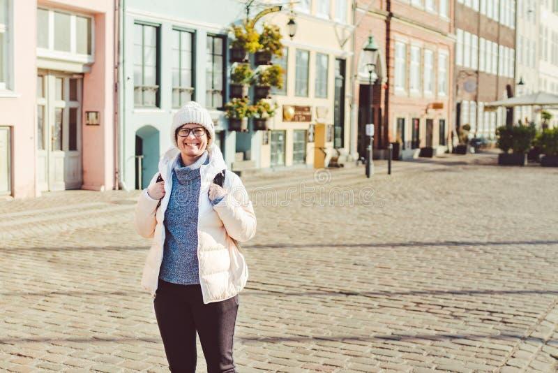 Ritratto di giovane turista europeo caucasico della donna in vetri per la vista di un cappello bianco e di un piumino con il nero fotografia stock
