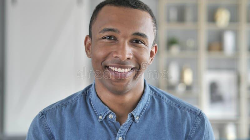Ritratto di giovane uomo africano sorridente che esamina macchina fotografica immagine stock libera da diritti