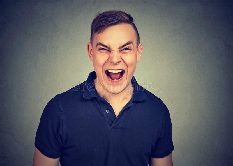 Ritratto di giovane uomo arrabbiato che grida fotografia stock libera da diritti