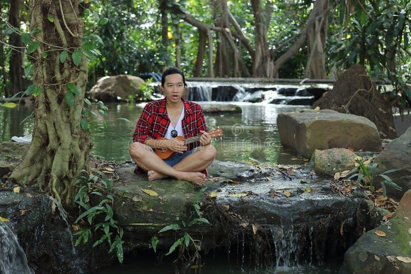 Ritratto di giovane uomo asiatico che gioca ukulele nel bello fondo della natura fotografia stock libera da diritti