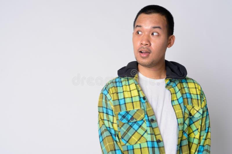Ritratto di giovane uomo asiatico dei pantaloni a vita bassa che pensa e che sembra colpito immagini stock