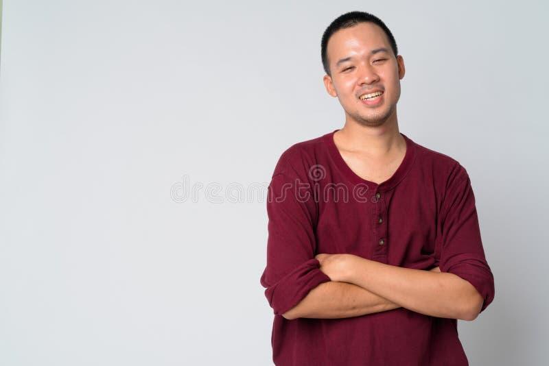 Ritratto di giovane uomo asiatico felice che sorride con le armi attraversate immagine stock libera da diritti