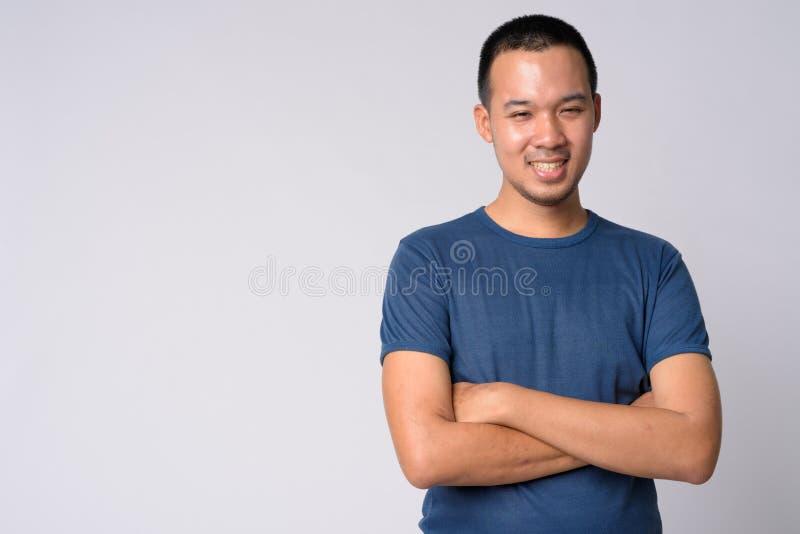 Ritratto di giovane uomo asiatico felice che sorride con le armi attraversate immagini stock