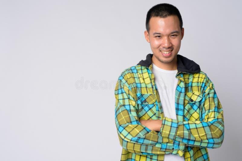 Ritratto di giovane uomo asiatico felice dei pantaloni a vita bassa che sorride con le armi attraversate immagini stock libere da diritti