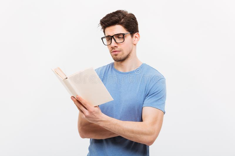 Ritratto di giovane uomo astuto in rea d'uso degli occhiali della camicia blu fotografia stock