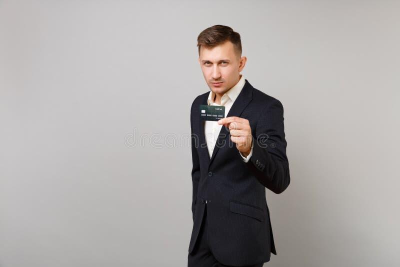 Ritratto di giovane uomo bello di affari in camicia nera classica del vestito che giudica la carta assegni di credito isolata sul fotografia stock