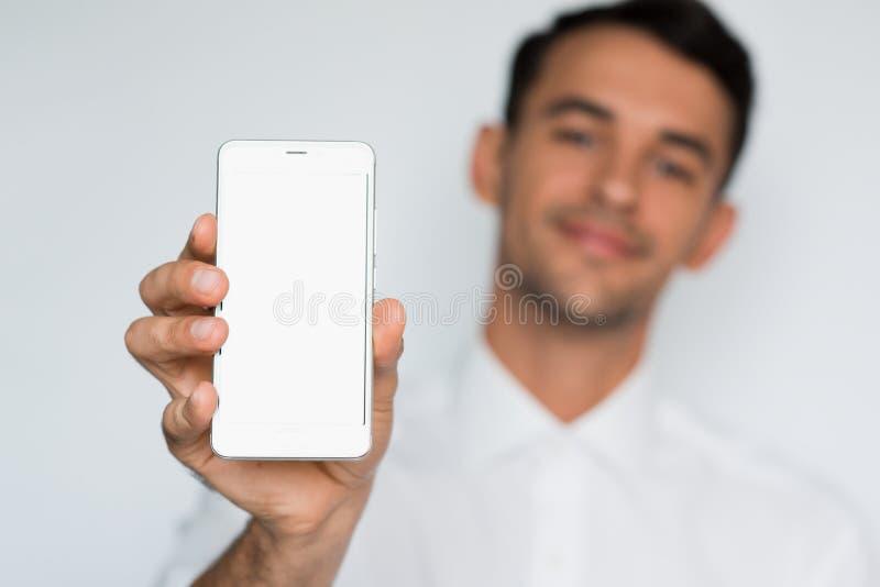 Ritratto di giovane uomo bello che mostra uno schermo in bianco dello Smart Phone isolato su un fondo grigio chiaro fotografia stock libera da diritti