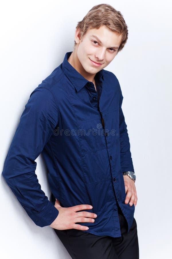 Ritratto di giovane uomo bello che porta camicia blu sopra fotografia stock