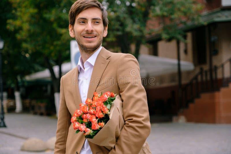 Ritratto di giovane uomo bello che sorride tenendo un mazzo di rose fotografie stock