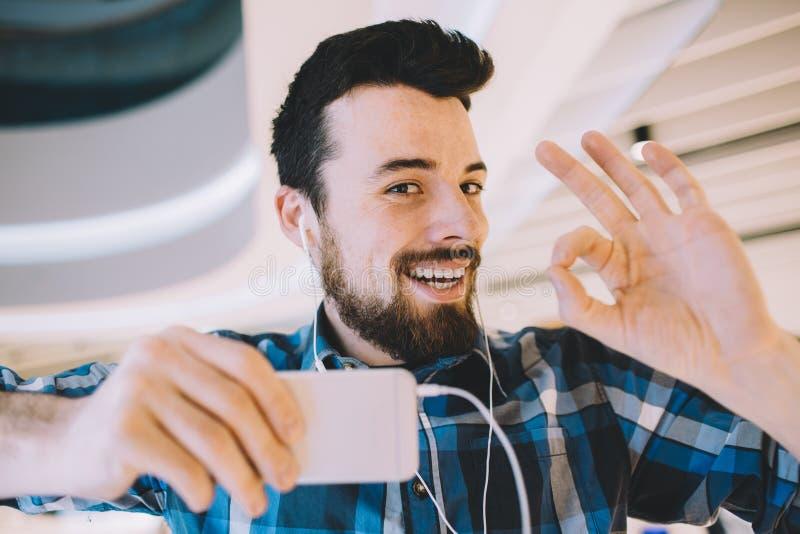 Ritratto di giovane uomo bello con il telefono e le cuffie nel fondo urbano immagine stock libera da diritti