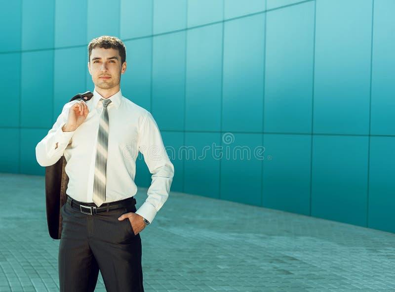 Ritratto di giovane uomo bello di affari vicino alla parete blu del busine fotografia stock