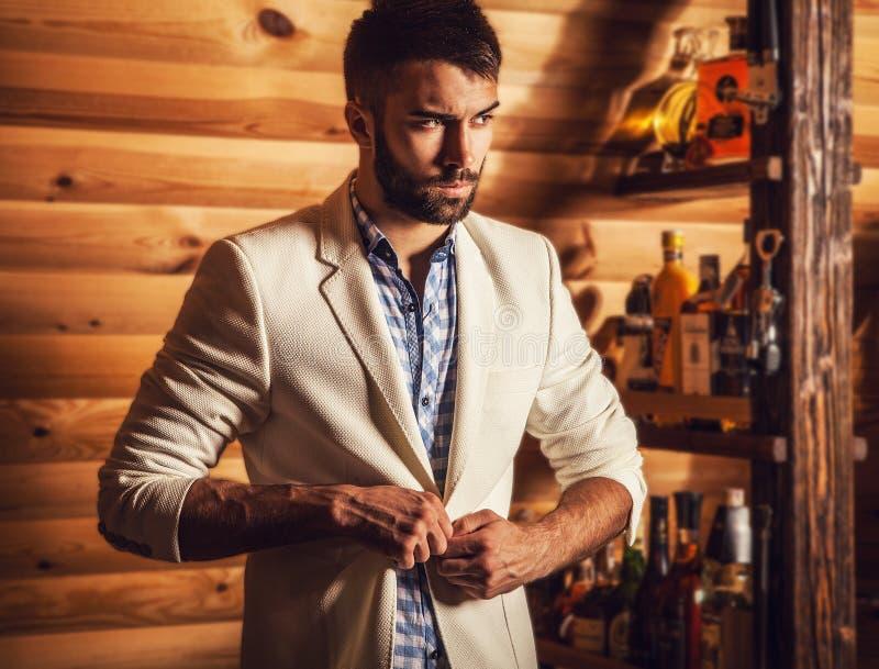 Ritratto di giovane uomo bello in vestito bianco vicino alla barra domestica fotografia stock
