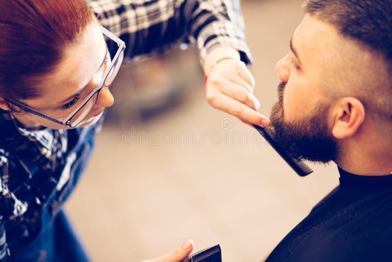 Ritratto di giovane uomo caucasico barbuto bello che ottiene taglio di capelli d'avanguardia nel negozio di barbiere moderno fotografie stock