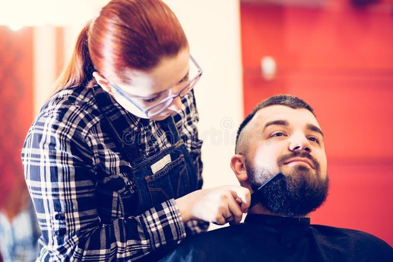 Ritratto di giovane uomo caucasico barbuto bello che ottiene taglio di capelli d'avanguardia nel negozio di barbiere moderno immagini stock