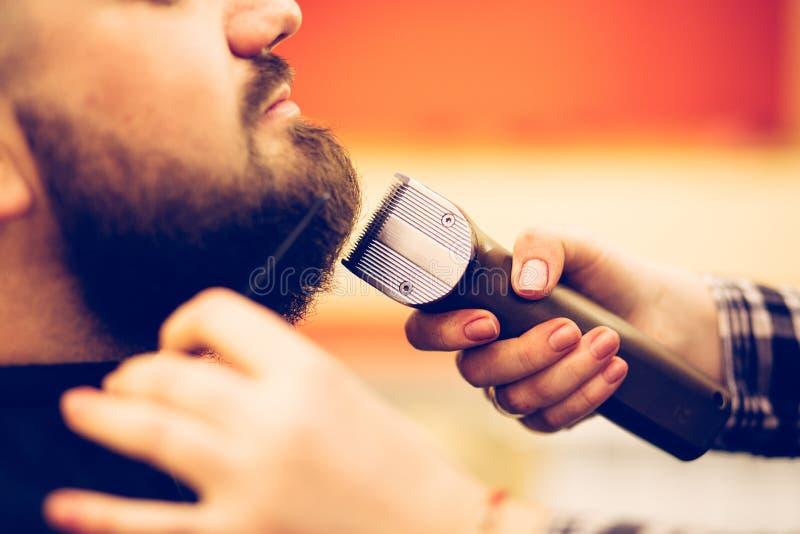 Ritratto di giovane uomo caucasico barbuto bello che ottiene taglio di capelli d'avanguardia nel negozio di barbiere moderno fotografie stock libere da diritti
