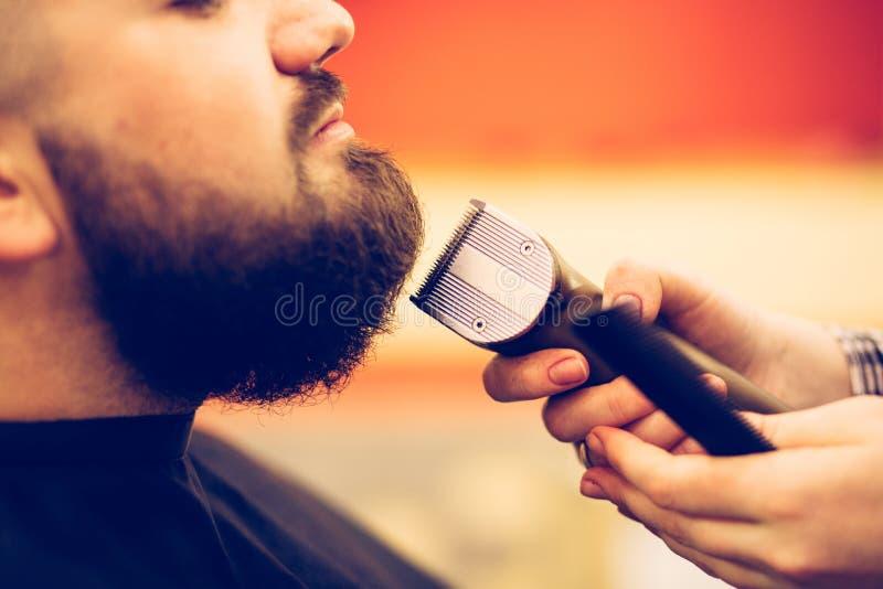 Ritratto di giovane uomo caucasico barbuto bello che ottiene taglio di capelli d'avanguardia nel negozio di barbiere moderno fotografia stock libera da diritti