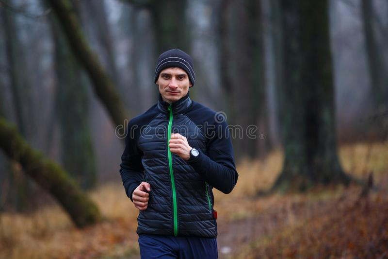Ritratto di giovane uomo corrente nel parco di autunno immagine stock