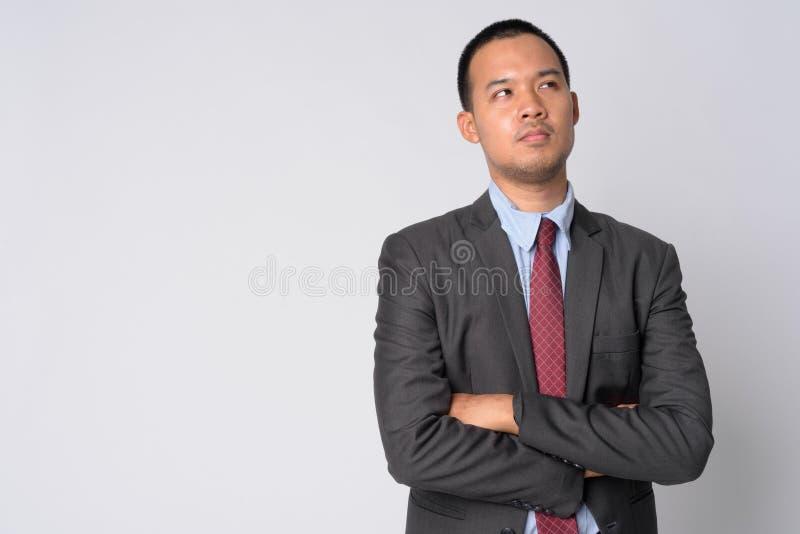 Ritratto di giovane uomo d'affari asiatico che pensa con le armi attraversate fotografie stock libere da diritti
