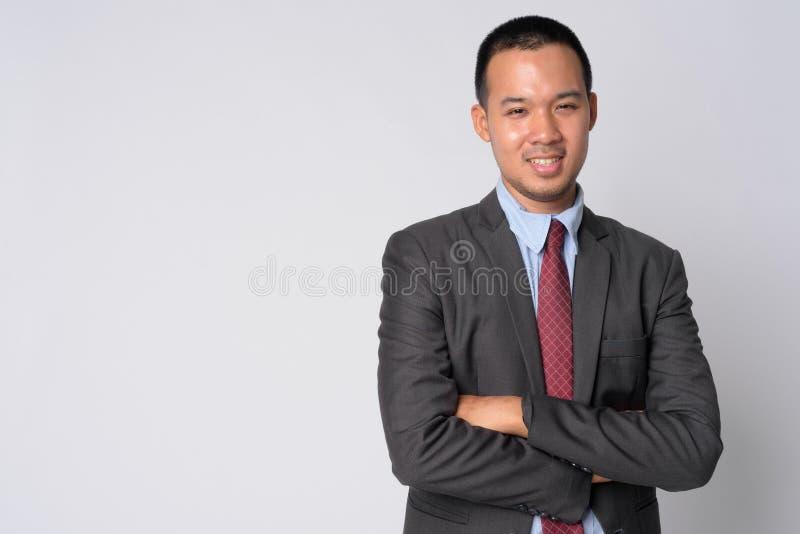 Ritratto di giovane uomo d'affari asiatico felice che sorride con le armi attraversate fotografia stock