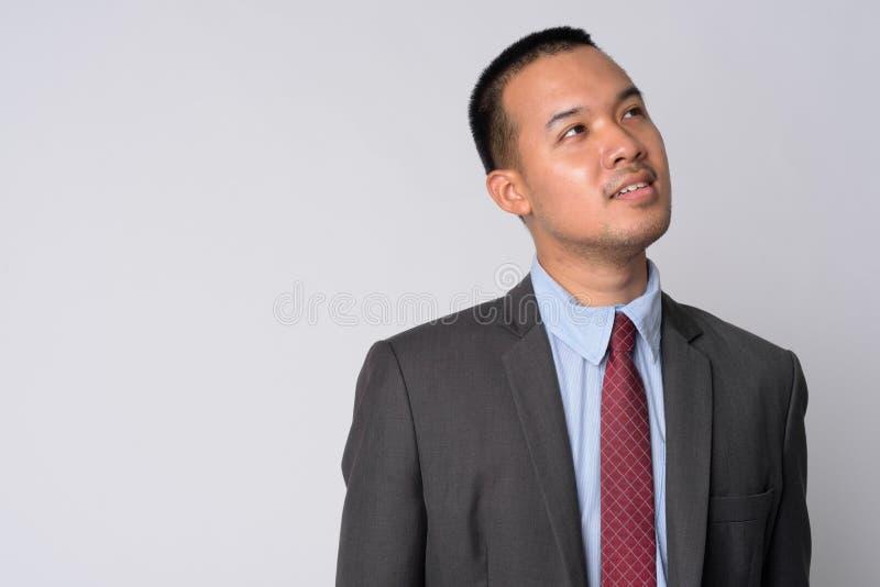 Ritratto di giovane uomo d'affari asiatico felice nel pensiero del vestito fotografia stock libera da diritti