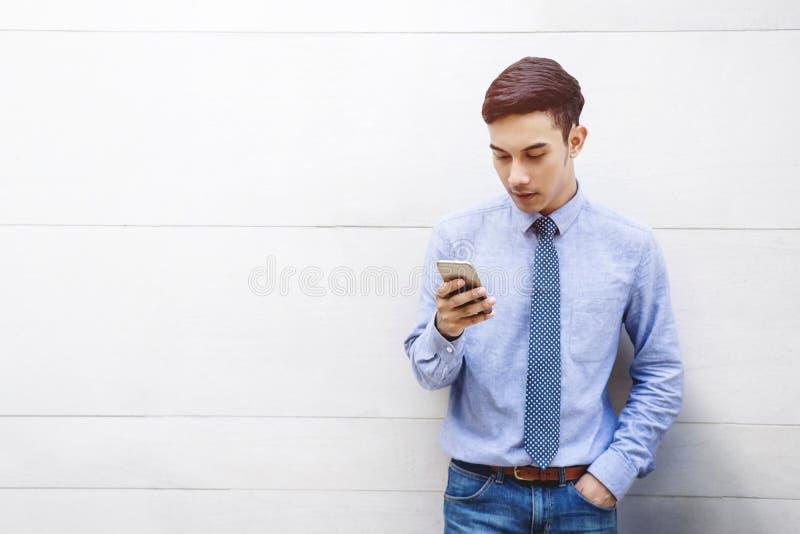 Ritratto di giovane uomo d'affari astuto facendo uso di Smartphone a costruzione fotografie stock libere da diritti
