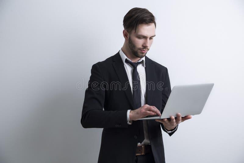 Ritratto di giovane uomo d'affari barbuto serio che sta vicino ad una parete bianca e che lavora con il suo computer portatile fotografie stock